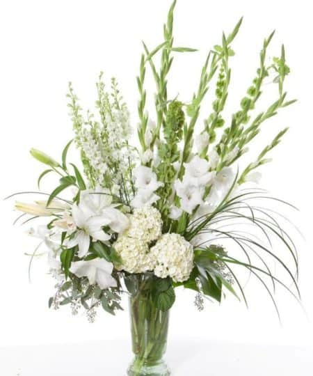 This all white arrangement makes a true statement, combining White Hydrangea, Larkspur, Lilies and other white flowers.